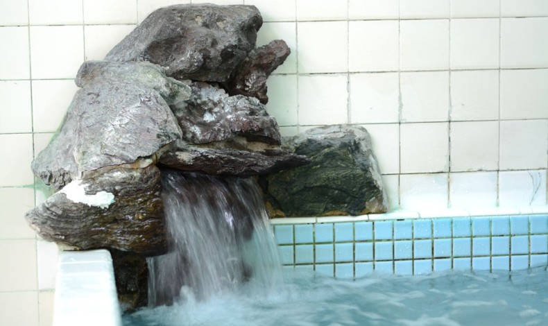 """""""天然石による給湯口もユニークです。毎週日曜日は薬湯です。"""""""